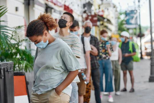 Young african american woman wearing mask waiting, standing in line with other people, respecting social distancing to collect takeaway order from the pickup point during lockdown