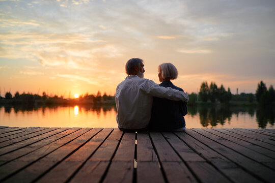 Romantic holiday. Senior loving couple sitting together on lake bank enjoying beautiful sunset.