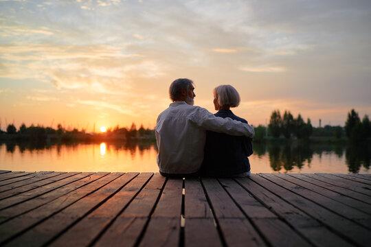 Romantic holiday. Senior loving couple sitting together on lake bank enjoying beautiful sunset.