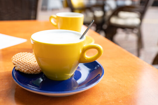 cappuccino in yellow cup. With typical Dutch caramel cookie called Stroopwafel