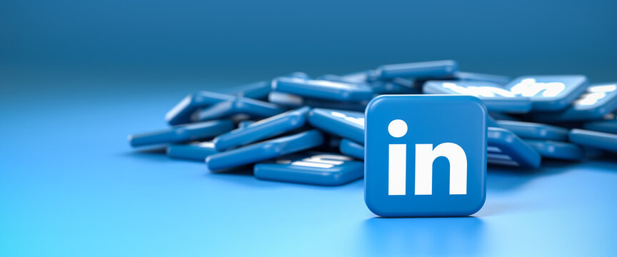 Logos of the business social media site and app LinkedIn on a heap. One tile standing upright in front. Web banner size with copy space - Selective focus