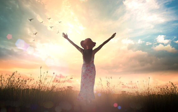 International women's day concept: Silhouette of healthy woman raised hands for praise and worship God at autumn sunset meadow background