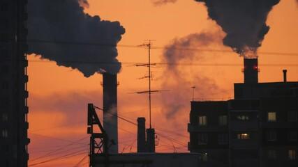 Fotobehang - Smoke pollution from smokestacks over urban buildings city skyline silhouette. 4K UHD Timelapse.