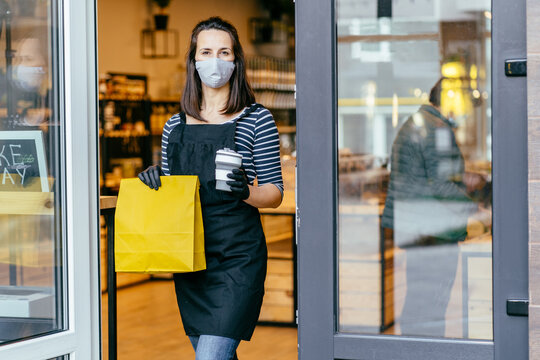 Grocery store owner working only with take away orders during coronavirus outbreak. Young woman worker wearing face protective mask giving coffee to customer. Healthcare and food, drinks concept.