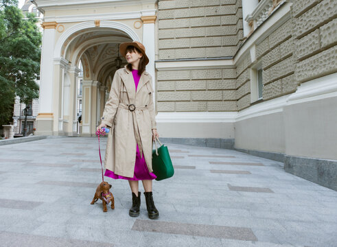 Walking with your pet. Woman walking with dachshund puppy on leash in city