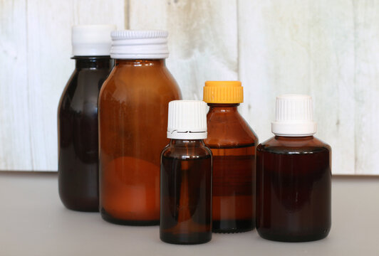 brown bottle with cough syrup on background