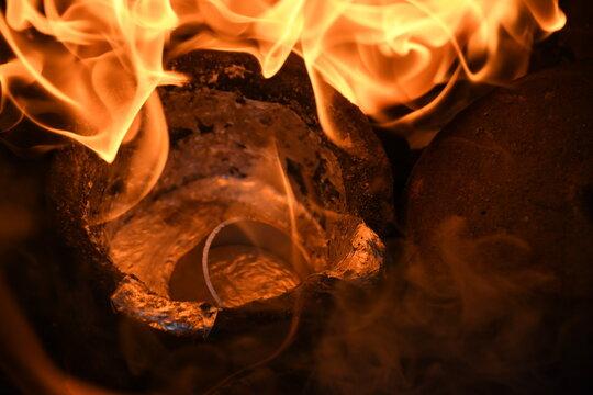 Aluminiumrohr wird in einem Schmelztiegel eingeschmolzen, umgeben von vielen orangefarbenen Flammen