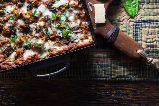 Hot, cheesy pasta bake in a cast iron pan. Quilted table runner on wooden table.