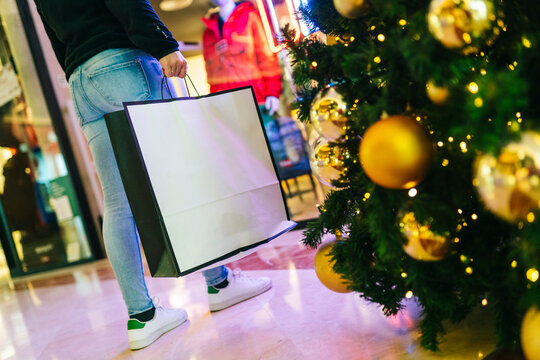 An unrecognizable person with a shopping bag in a mall at christmas
