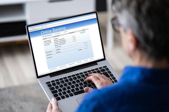Man Using Tablet Computer Checking Bank Statement