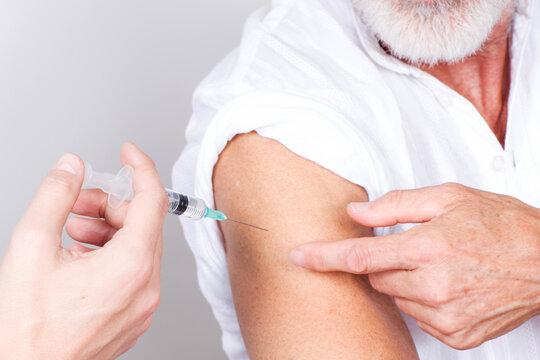 Setting a coronavirus vaccine in the arm of an elderly man with a grey beard