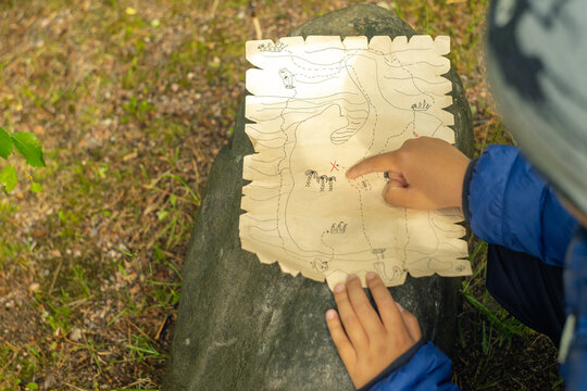 A child is looking for a treasure of pirates with a paper map