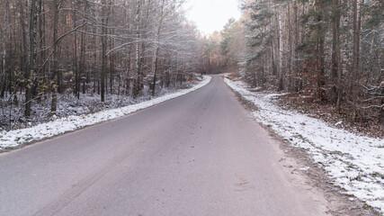 Leśna droga pokryta śniegiem o poranku