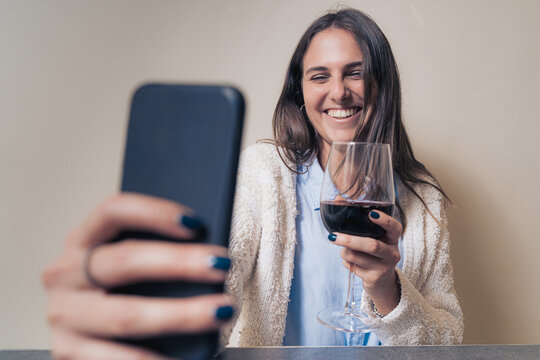 young woman smiling and clinking online with red wine having a video call with her friends online during coronavirus pandemic