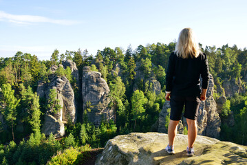 Fototapeta Woman looking at the sandstone rock in Prachovske skaly, Bohemian Paradise (Cesky Raj), Czechia.