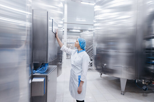 Worker female operator in uniform uses process control panel food factory production line and steel tanker