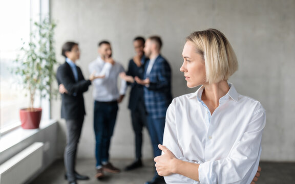 Male Coworkers Whispering Behind Back Of Unhappy Businesswoman In Office