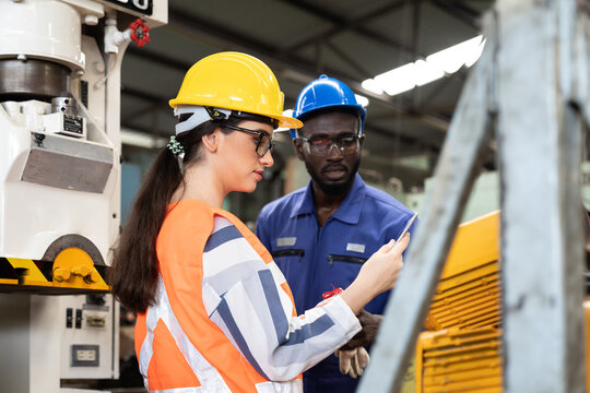 African American male and female industrial engineering in safety uniform, hard hats working and discussing in the heavy industry manufacturing factory