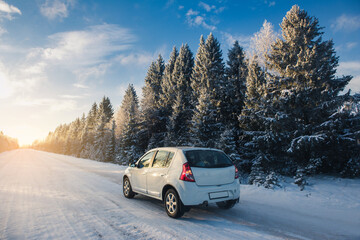 Car on a winter road through a snow covered forest.