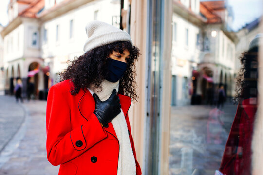 Portrait of a  woman in red shopping outside with face mask  looking at shop window