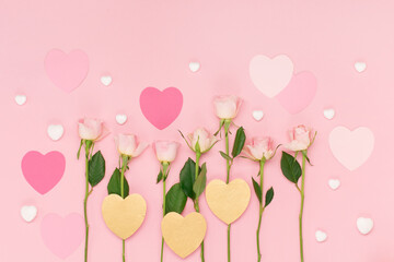 Pink paper hearts and flowers roses on pastel pink background. Valentines day concept. Flat lay, top view, copy space