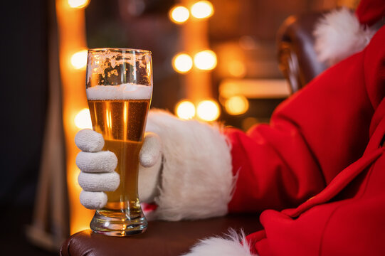 Close-up of santa claus hand with a pint of light beer. Merry Christmas