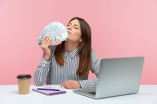 Excited rich business woman enjoying smell of hundred dollar bills holding cash in hand sitting at workplace, crazy about big profit. Indoor studio shot isolated on pink background