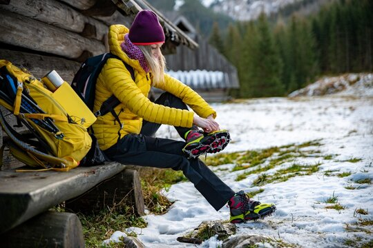Woman hiker in a yellow down jacket puts yellow crampons on her shoes before going to the mountains. The backpack with equipment is lying next to it.