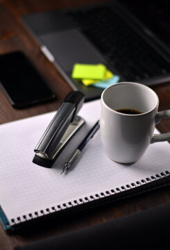 Coffee and office supplies on a wooden table