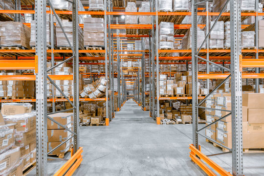 Large warehouse. Tall and long metal racks filled with various boxes, containers and drawers