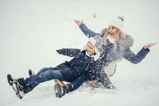 Beautiful mother in a blue jacket. Family sledding in a winter park. Little boy in a cute hat