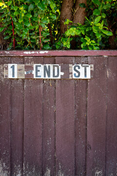 """A broken street address that now reads """"1 End Street"""" which could represent an end of things. Brown dirty fence with leaves and cobwebs, vertical"""