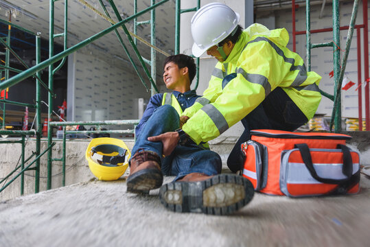 Accident at work of construction worker at site. Builder accident falls scaffolding on floor, Safety team helps employee accident. Add zoom filter effect for movement feeling.