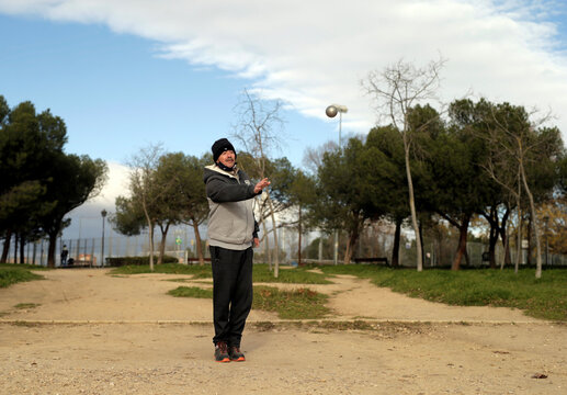 Man throws petanque boules in a park in Madrid