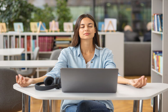 Beautiful happy young woman or student female meditates at the workplace