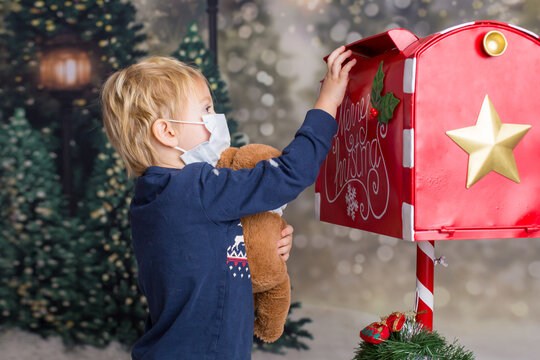 Little cute toddler child, sweet blond boy, sending letter to Santa Claus, wearing medical mask and holding teddy bear