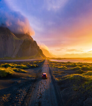 Gravel road at sunset with Vestrahorn mountain and a car driving, Iceland