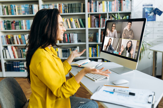 Caucasian young woman in casual stylish clothes communicating with her colleagues or friends by video conference while sitting at the table at home