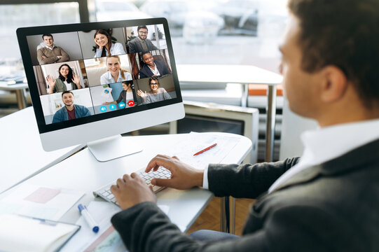 Online video meeting. Successful young adult businessman communicate with  business colleagues by video call using computer discussing about financial graphs and strategy