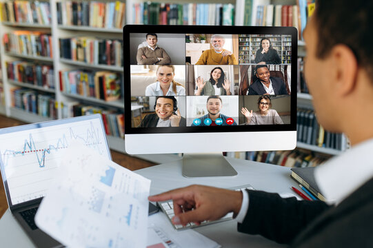Multi ethnic business people gathered together in online video conference discuss financial strategy, colleagues have distant webcam conference with financial graphs