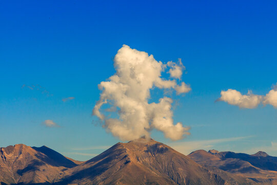 Curious shaped clouds on top of a mountain. Nature elements concept