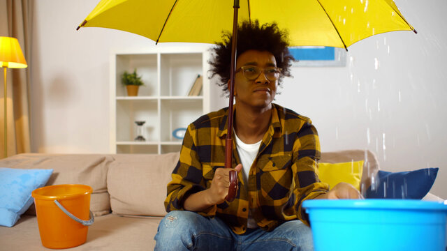 African guy at home under umbrella holding plastic bucket collecting water falling from ceiling.