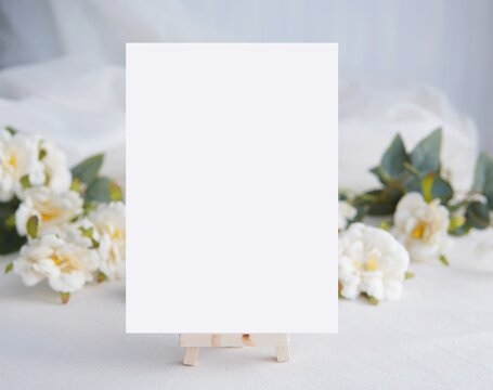 White empty vertical card mockup, wedding invitation template, menu card, white flowers on background.