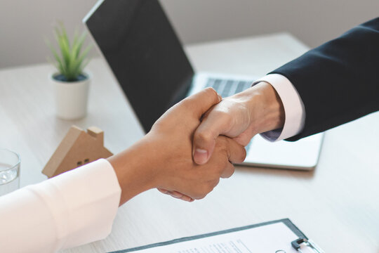 Closed up of house agent handshake  to congratulate customer on becoming a new landlord.