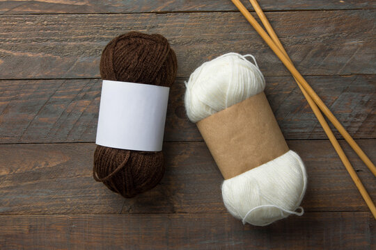 White and brown skeins of hand spun yarn with blank Kraft paper wrap labels for mockup on rustic wooden table with needles. Knitting crafts product packaging concept