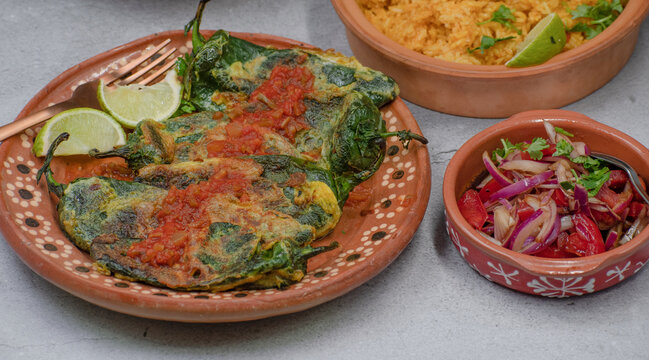 Traditional mexican stuffed peppers chiles rellenos on mexican clay plate along with rice and salad