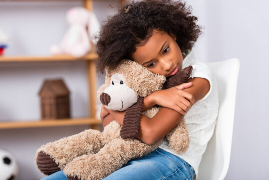 Depressed african american girl with autism hugging teddy bear while sitting on chair with blurred office on background