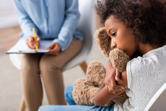 Upset african american girl with autism hugging teddy bear during consultation with blurred psychologist on background