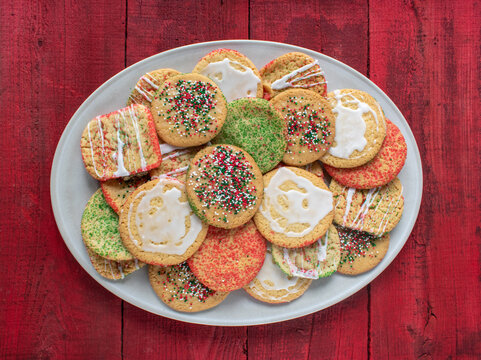 oval platter of a variety of simple sugar cookies with sprinkles and icing flat lay