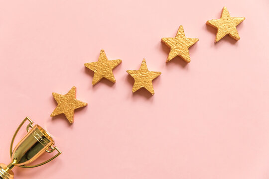 Simply flat lay design winner or champion gold trophy cup and 5 stars rating isolated on pink pastel background. Victory first place of competition. Winning or success concept. Top view, copy space
